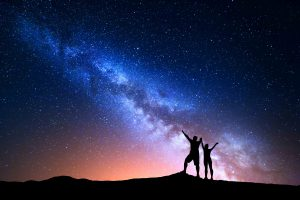 Couple holding hands enjoying colorful night sky
