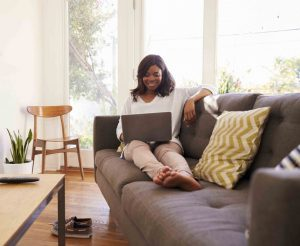Woman sitting on sofa working happily at her computer