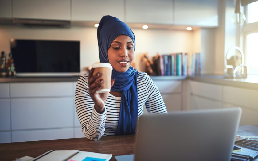 Young Arabic female entrepreneur wearing a hijab working on a laptop and drinking coffee while sitting at a table in her kitchen