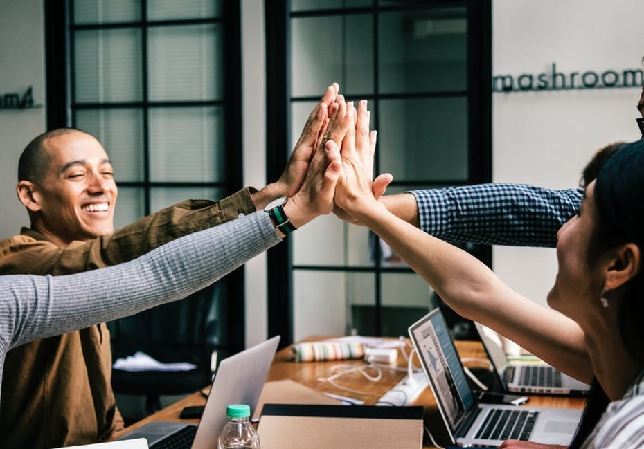 soft skills showing coworkers collaborating and giving high fives