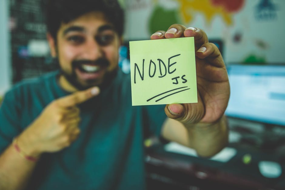 web developer pointing to a post-it note that says node js for is javascript easy to learn