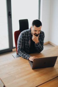 man working at computer wondering if python is hard to learn