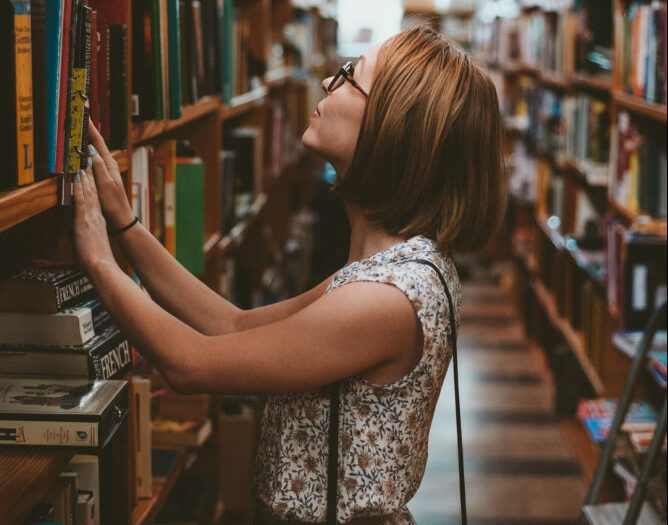 woman looking at books in library